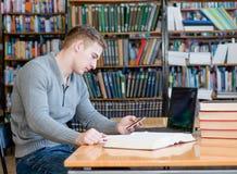 Estudiante masculino que manda un SMS en el teléfono en la biblioteca de universidad Fotos de archivo