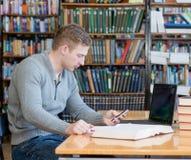 Estudiante masculino que manda un SMS en el teléfono en la biblioteca de universidad Imagenes de archivo