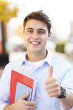 Estudiante masculino que muestra los pulgares para arriba Fotos de archivo
