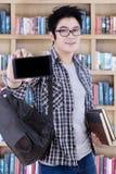 Estudiante masculino que muestra un smartphone en la biblioteca Imágenes de archivo libres de regalías