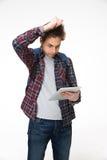 Estudiante masculino que se coloca con la tableta Foto de archivo libre de regalías