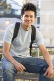 Estudiante masculino que se sienta afuera Foto de archivo