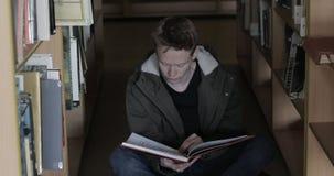 Estudiante masculino que se sienta en el libro de lectura del piso de la biblioteca almacen de video