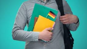 Estudiante masculino que sostiene los cuadernos con la bandera alemana, programa educativo internacional metrajes