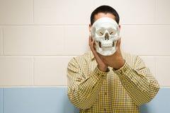 Estudiante masculino que sostiene un cráneo humano foto de archivo