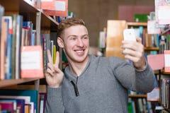 Estudiante masculino que toma el selfie en biblioteca de universidad Imagenes de archivo