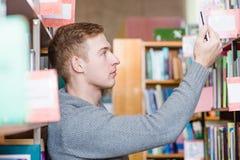 Estudiante masculino que toma el selfie en biblioteca de universidad Imágenes de archivo libres de regalías