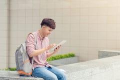 Estudiante masculino que usa la tableta digital en campus de la universidad Fotografía de archivo