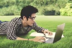Estudiante masculino que usa un ordenador portátil en el parque Fotografía de archivo