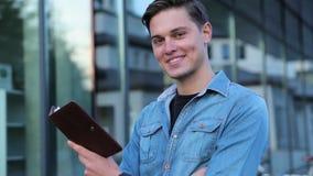 Estudiante masculino Reading Notepad Outdoors en la universidad almacen de video