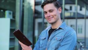 Estudiante masculino Reading Notepad Outdoors en la universidad almacen de metraje de vídeo