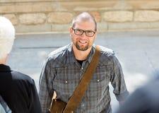 Estudiante masculino sonriente With Bag Standing en campus Fotos de archivo libres de regalías