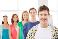 Estudiante masculino sonriente con el grupo de compañeros de clase Imágenes de archivo libres de regalías