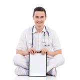 Estudiante masculino sonriente de la medicina que sostiene un tablero Fotos de archivo libres de regalías