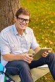 Estudiante masculino sonriente en lentes con PC de la tableta Fotografía de archivo