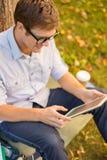 Estudiante masculino sonriente en lentes con PC de la tableta Imagenes de archivo
