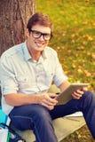Estudiante masculino sonriente en lentes con PC de la tableta Fotografía de archivo libre de regalías