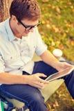 Estudiante masculino sonriente en lentes con PC de la tableta Imagen de archivo libre de regalías