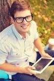 Estudiante masculino sonriente en lentes con PC de la tableta Imagen de archivo