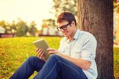 Estudiante masculino sonriente en lentes con PC de la tableta Imágenes de archivo libres de regalías