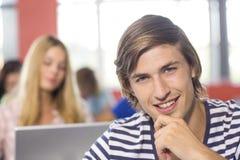 Estudiante masculino sonriente en sala de clase Foto de archivo libre de regalías