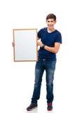 Estudiante masculino sonriente que lleva a cabo al tablero en blanco Fotos de archivo