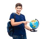 Estudiante masculino sonriente que señala el finger en el globo Imagen de archivo libre de regalías