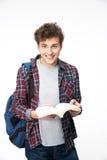 Estudiante masculino sonriente que se coloca con el libro abierto Imágenes de archivo libres de regalías