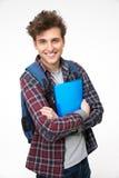 Estudiante masculino sonriente que se coloca con las carpetas Foto de archivo libre de regalías