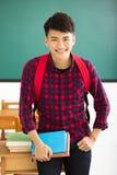 Estudiante masculino sonriente que se coloca en sala de clase Fotografía de archivo libre de regalías