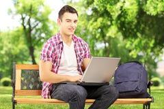 Estudiante masculino sonriente que se sienta en un banco y que trabaja en un ordenador portátil Fotografía de archivo