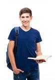 Estudiante masculino sonriente que sostiene el libro Imagen de archivo libre de regalías