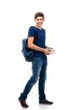 Estudiante masculino sonriente que sostiene los libros Imagen de archivo