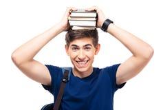 Estudiante masculino sonriente que sostiene los libros en la cabeza Imagenes de archivo