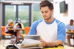 Estudiante masculino Studying In Classroom con la tableta de Digitaces fotografía de archivo libre de regalías