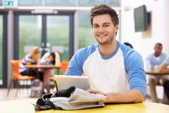 Estudiante masculino Studying In Classroom con la tableta de Digitaces Imágenes de archivo libres de regalías
