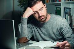 Estudiante masculino subrayado que estudia tarde en la noche Imagenes de archivo