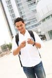 Estudiante masculino Texting en la escuela Imágenes de archivo libres de regalías