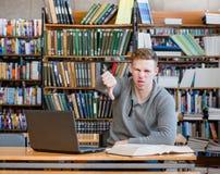 Estudiante masculino trastornado con en la biblioteca que muestra el pulgar abajo Fotos de archivo