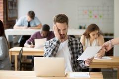 Estudiante masculino trastornado subrayado sobre marca del examen Imágenes de archivo libres de regalías