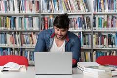 Estudiante masculino Typing en el ordenador portátil en la biblioteca de universidad imágenes de archivo libres de regalías