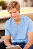 Estudiante masculino Using Digital Tablet de la High School secundaria al aire libre foto de archivo