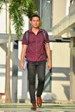 Estudiante masculino Walking On Campus de la universidad impasible imagen de archivo libre de regalías
