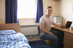 Estudiante masculino Working In Bedroom del alojamiento del campus imagen de archivo libre de regalías