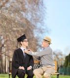 Estudiante masculino y su padre orgulloso que se sientan en parque Foto de archivo