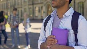 Estudiante mezclado que se mantiene aparte, mirando a la gente que habla en la parte posterior, diferente almacen de metraje de vídeo