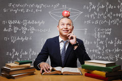 Estudiante miling de pensamiento con la manzana en la cabeza que se prepara para probar Foto de archivo libre de regalías