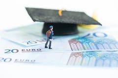 Estudiante miniatura que se coloca encima de 20 billetes de banco euro que miran el birrete Imagenes de archivo