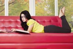 Estudiante moderno que estudia en el sofá Imagenes de archivo