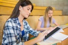 Estudiante moreno bonito que usa la tableta Fotos de archivo libres de regalías